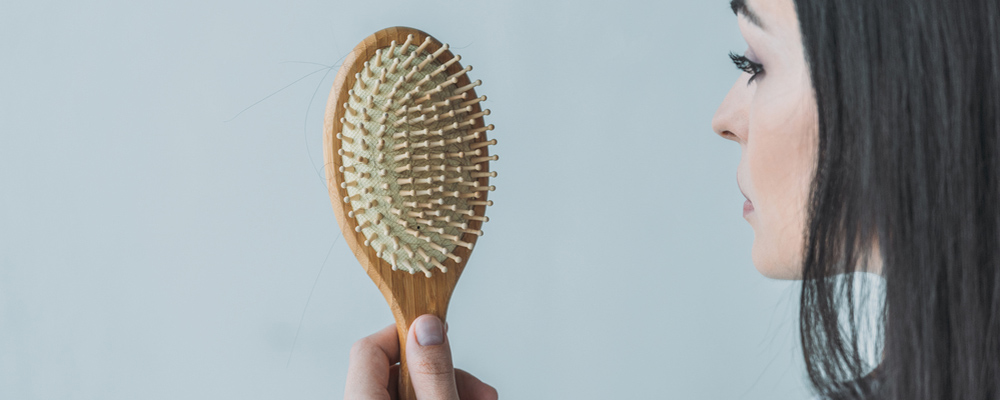 Cropped shot of brunette woman holding hairbrush