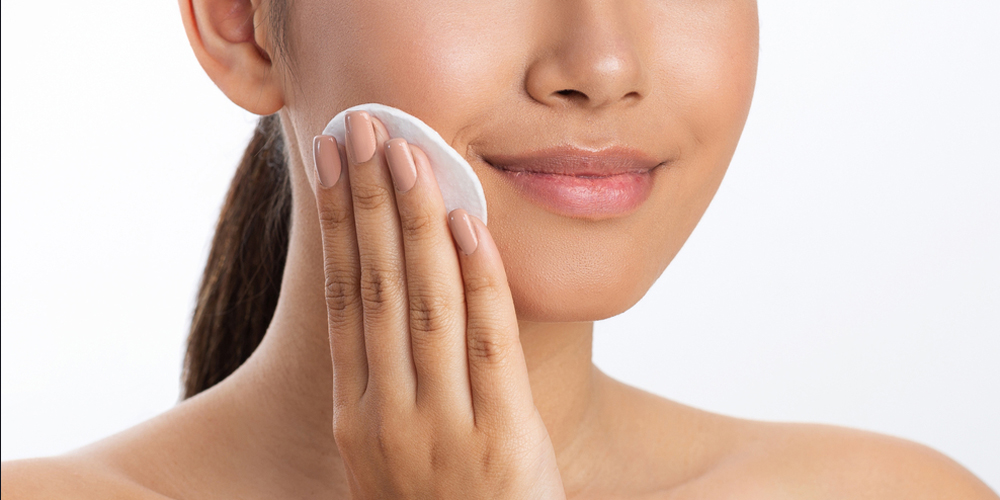 Girl applying lotion using cotton pad, white background