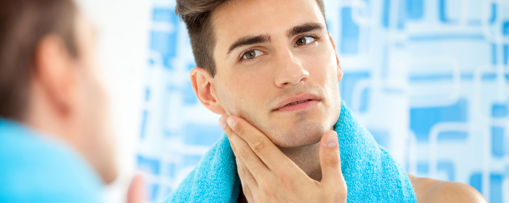 Young handsome man touching his smooth face after shaving