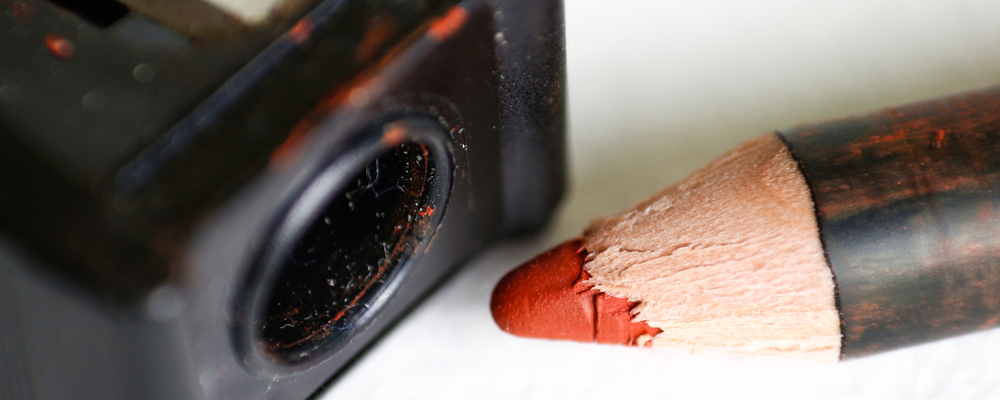 Red pencil for makeup and sharpener. Macro. Closeup. Isolated on a white background.