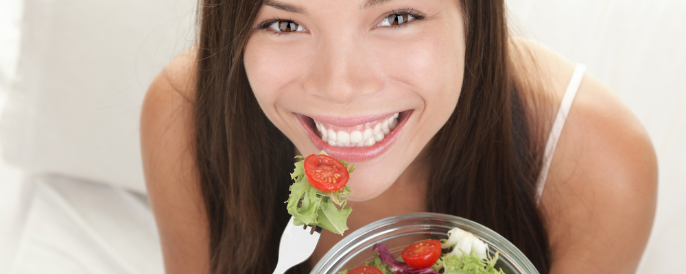 Woman eating salad. Portrait of beautiful smiling and happy mixed Asian Caucasian woman enjoying a healthy salad and cherry tomatoes snack.
