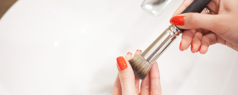 Makr up brush. Woman washing dirty makeup brush with soap and foam in the sink.