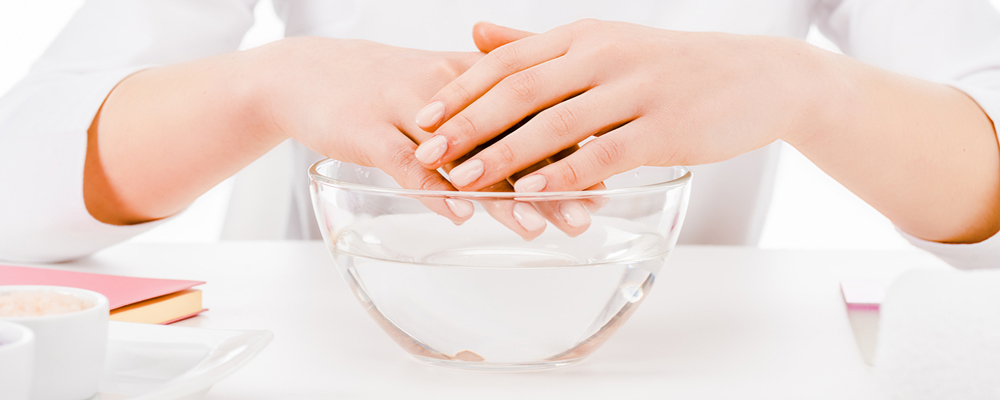 Woman's hand over the bowl with water