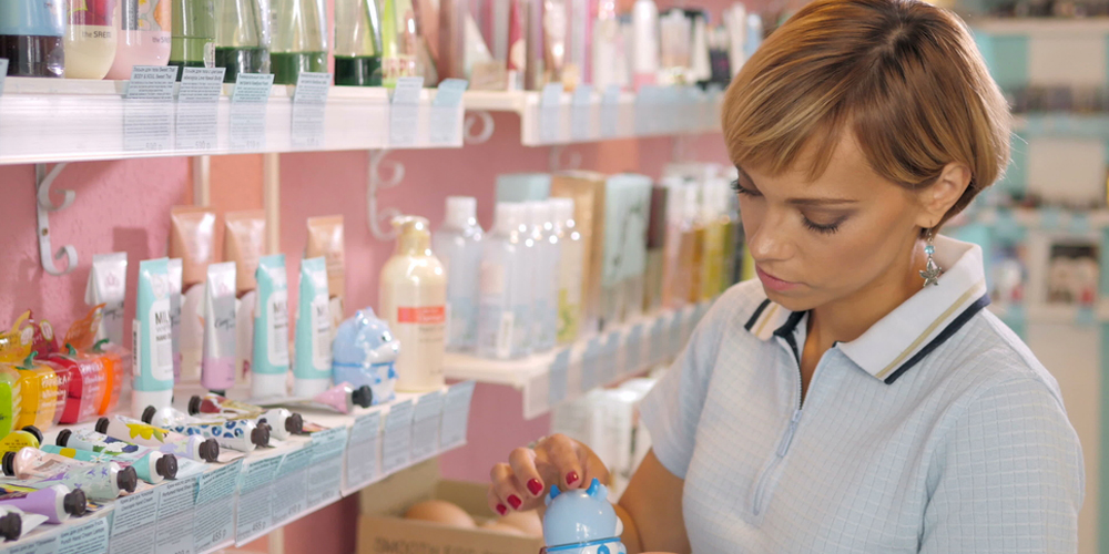 Young woman choosing cosmetic cream beauty shop.