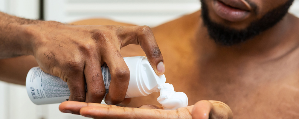 African american man putting shaving foam on palm, preparing to shave at bathroom