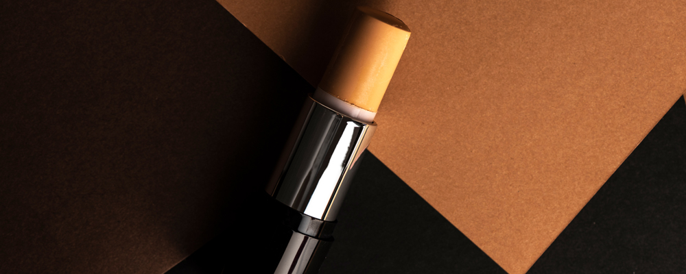 concealer stick, on geometric backgrounds, in shades of brown. Product and makeup concept from above