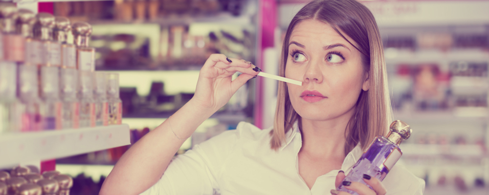 Girl smelling perfume testers in cosmetics store looking for stylish fragrance