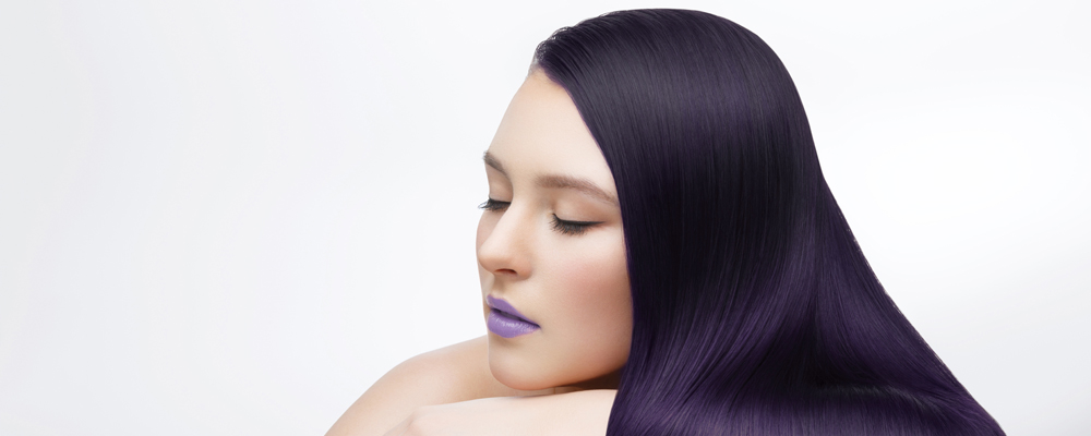 beautiful young woman with long healthy shiny hair. purple color. eyes closed. studio beauty shot. copy space.