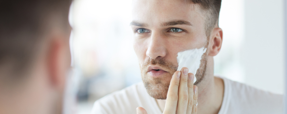 Head and shoulders portrait of handsome young man applying shaving cream looking at his reflection in mirror, copy space