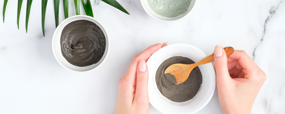 Preparing cosmetic clay mask in bowl. Natural organic SPA beauty products on marble background, facial skin care concept.