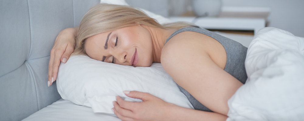 Young beautiful blonde woman sleeping in her bedroom and relaxing in the morning.