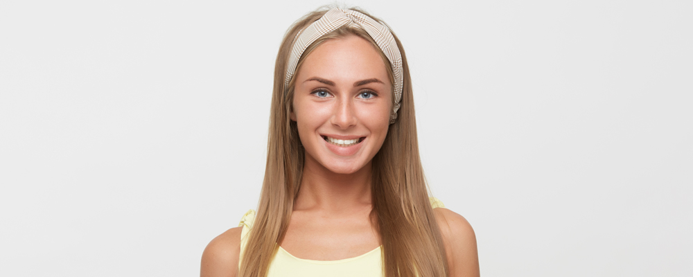 Indoor photo of young lovely happy woman with long blonde hair showing her pleasant emotions while posing over white background, keeping her hands along body