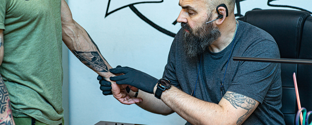 Tattoo salon. Master with a beard looks at the hand of the client's man. Preparing for new tattoo.