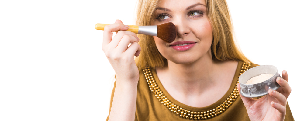 Fashionable cheerful young female holding professional powder brush, adding last touch to her make up