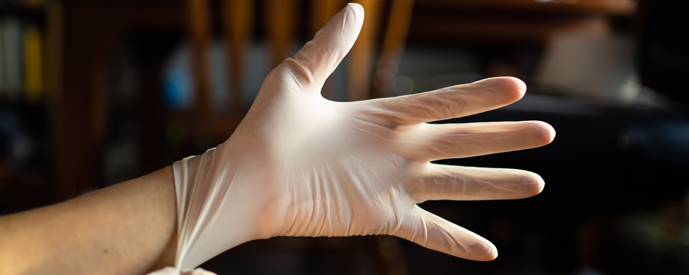 wearing disposable latex gloves to avoid the contact with viruse