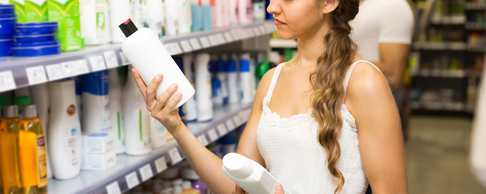 Young woman choosing shampoo at supermarket