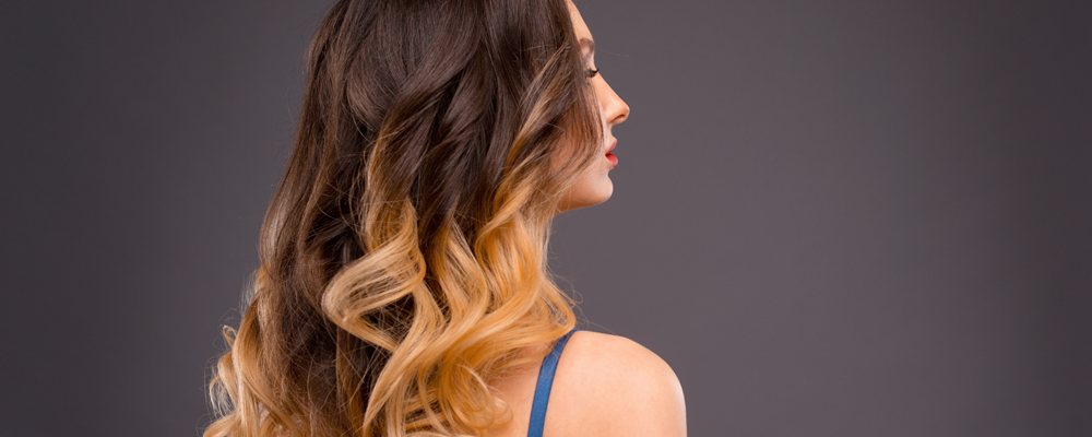 Woman with Long Healthy Colorful Ombre Wavy Hair. Close Up of Ha