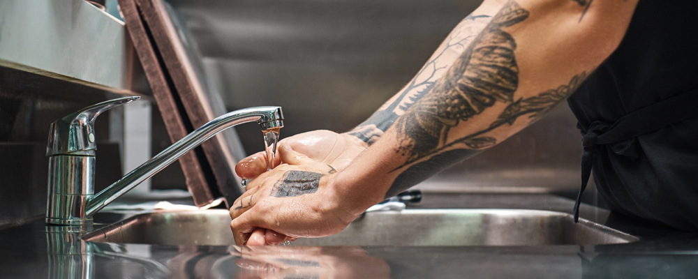 Before cooking...Close up photo of chef carefully washing his hands with different tattoos in a restaurant kitchen. Cropped view