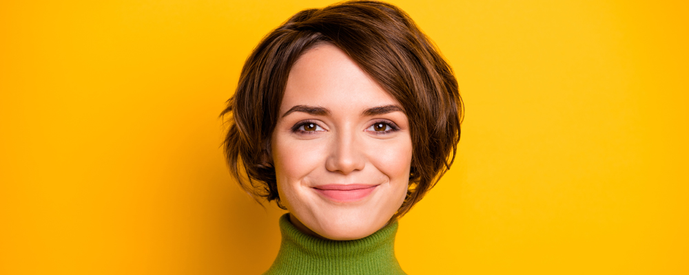 Closeup photo of funny short hairdo lady charming smiling good mood positive, person wear casual green turtleneck warm sweater isolated yellow color background
