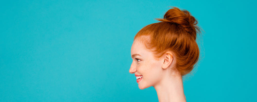 Profile side view portrait of nice stylish adorable attractive magnificent pretty cheerful glad positive optimistic red-haired girl with bun, isolated on bright vivid blue background